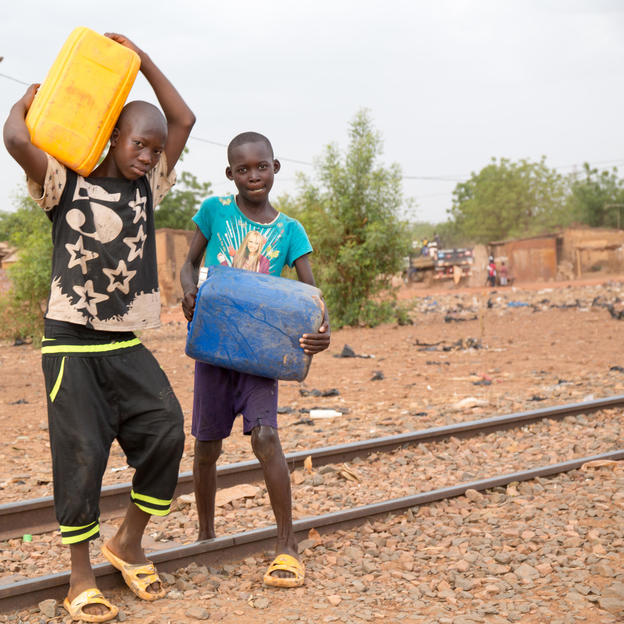 Cheick and his friend carrying cans of water and crossing the railway to go home, in the Region of Koulikoro, Mali, May 2017
