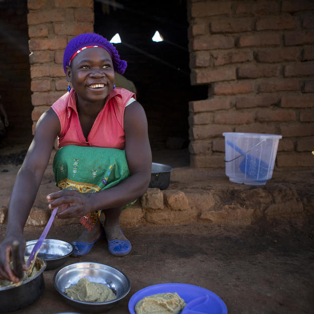 Zione Petulo, 20, prepares breakfast for the family using clean water, at home in the village of Chandaka, Salima, Malawi, June 2016.