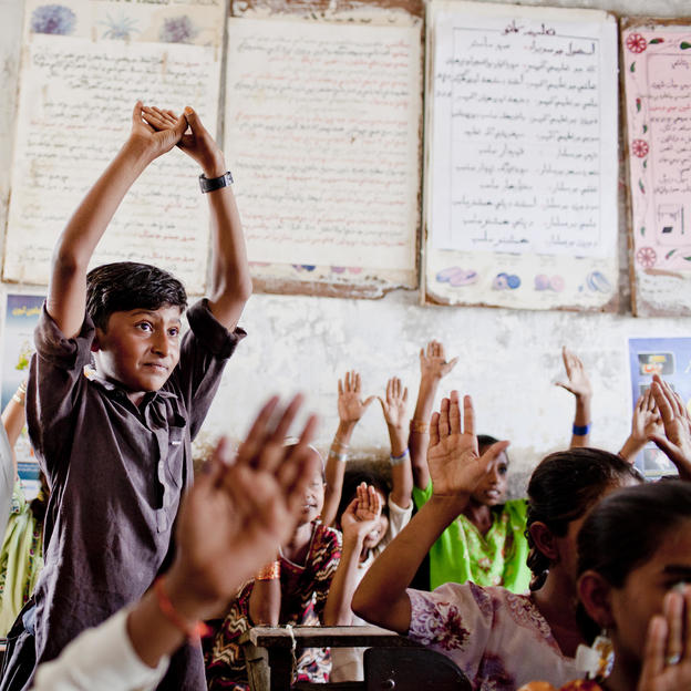 Students at school in Pakistan raise their hands in agreement that they will follow good hygiene practices.