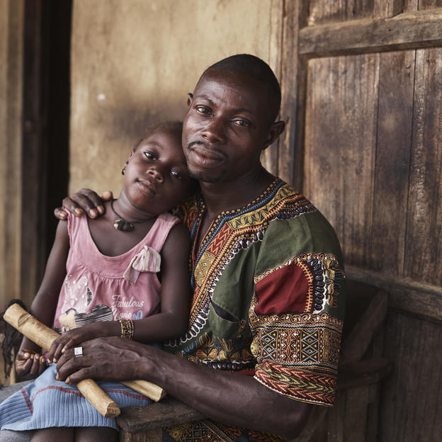 Sellu with his daughter Nancy, 6 outside their home in Tombohuaun.