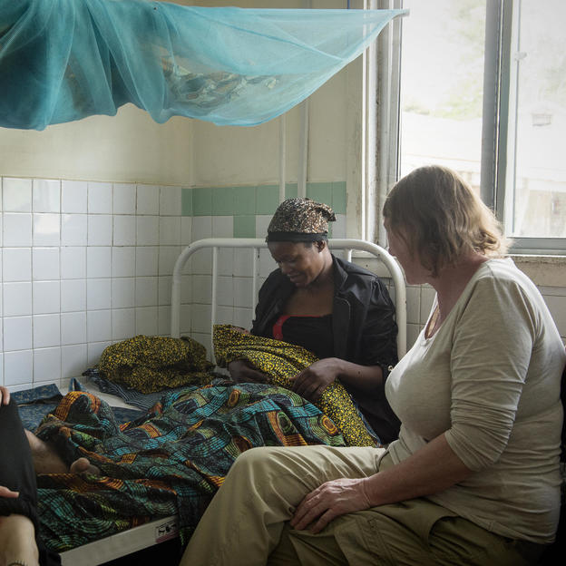 Midwives Cheryl Stanley (left) and Delia Jepson (right) sit with 21-year-old Mary Samson Gunda at her bedside at Kiomboi Hospital, Iramba, Tanzania, January 2016.