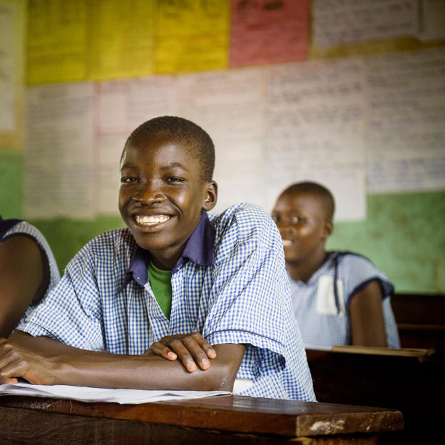 Dennis, 14, WASH Club member (front R) sitting in a class at St Mary's School, Uganda.