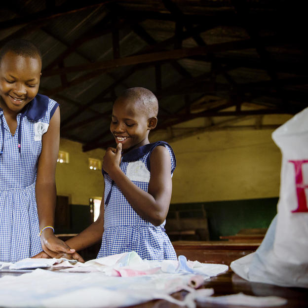 Esther, WASH Club member teaches Rosemary how to make sanitary pads at St Mary's School, Uganda.