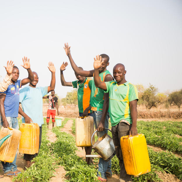 Moustapha and his colleague gardners posing togteher with watering cans in their garden, Burkina Faso.