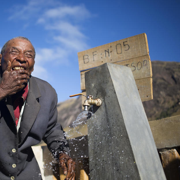 Rakotondrahasy, 81 years old, washes his face with clean water at the water point in  his village in Ankazobe district, Madagascar