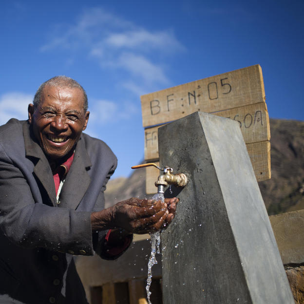 Rakotondrahasy, 81, washing his face and drinking clean water at their water point in Ankazobe district, Madagascar