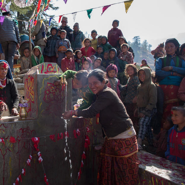 A woman is happy to see water running from the tap for the first time. Baragaun, Nepal