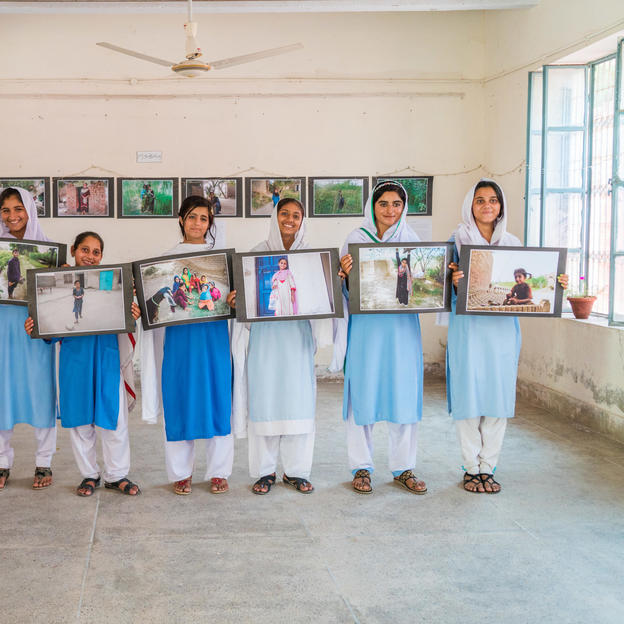 Participants holding their photographs during the photography exhibition in School, Pakistan.