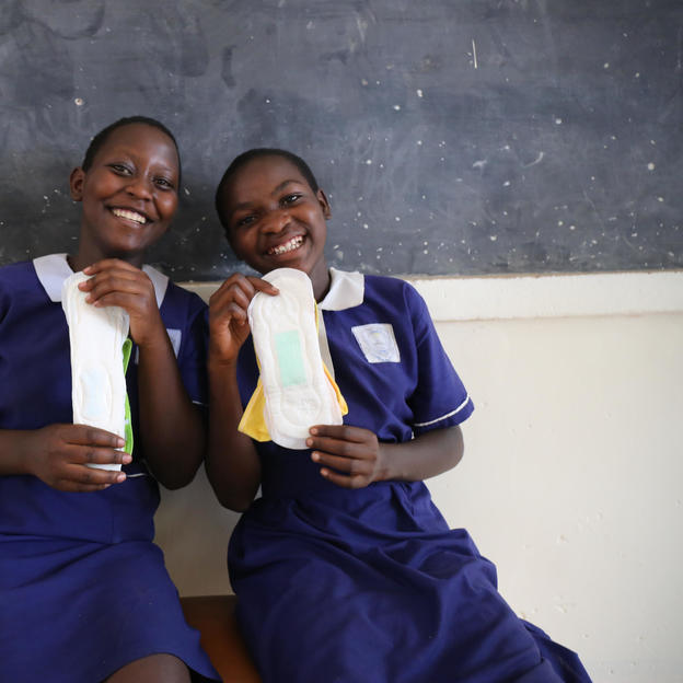 Friends Racheal and Florence hold sanitary pads in their classroom in Uganda.