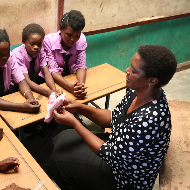 Alice teaches school girls about sanitary pads in Zambia.