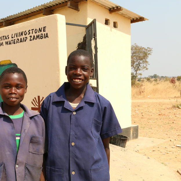 Evan and Friday stand near their newly constructed latrine for boys in Zambia.