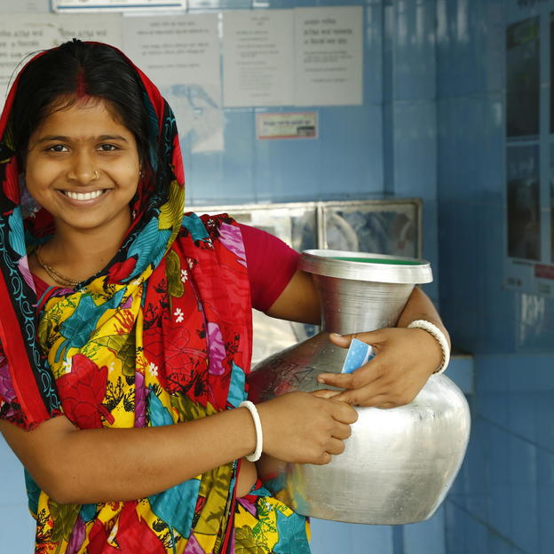 Shusmita, 18, poses for a photograph after collecting water from the ATM machine at Chalna Bazar, Bangladesh.