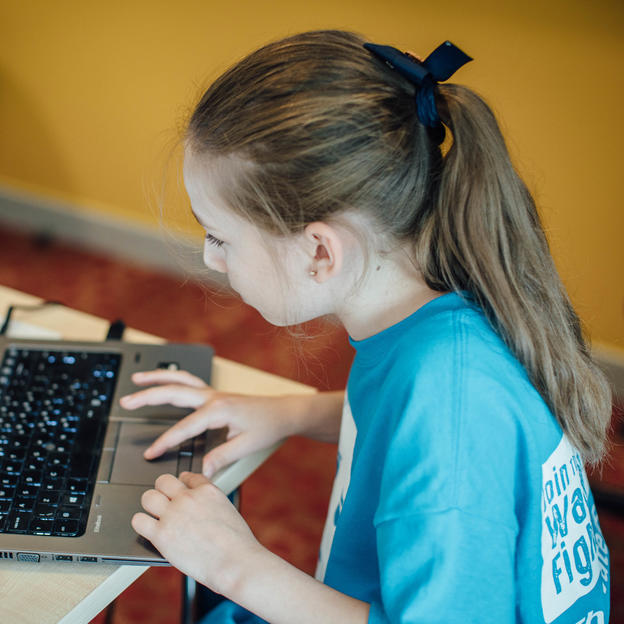 A young girl plays WaterAid's Angry Turds game on a laptop