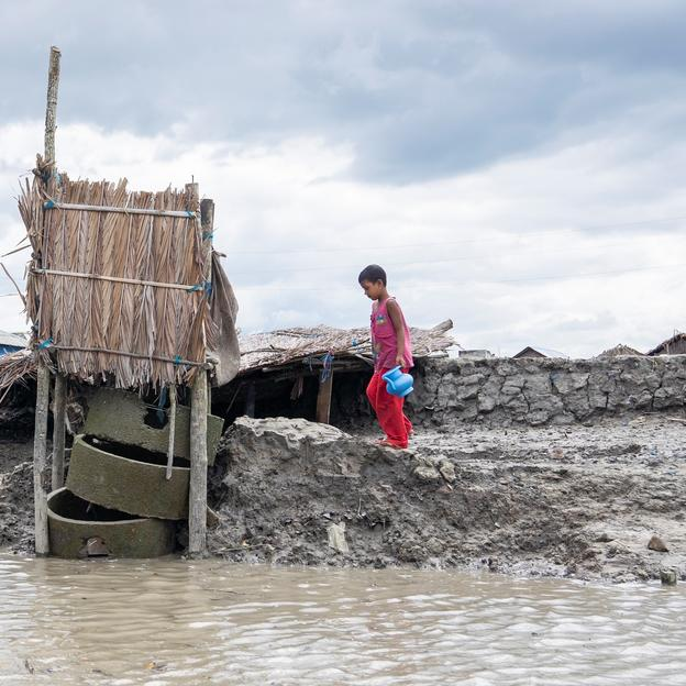 A child uses an outdoor latrine which is often overflown due to tidewater in Khulna, Bangladesh, where sea-level have risen.