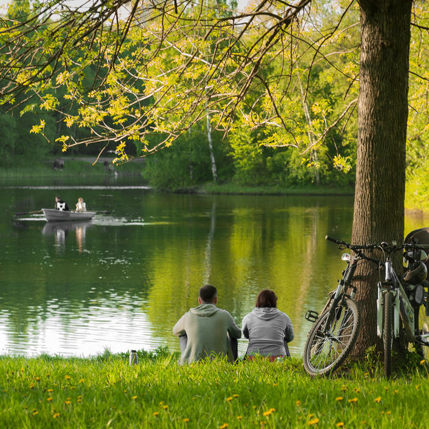 A couple sit by the edge of a lake with their bikes