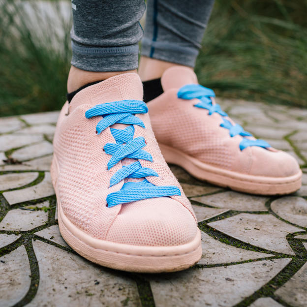 A pair of trainers laced up with exclusive March for Water blue shoelaces
