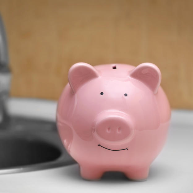 A running tap and a piggy bank