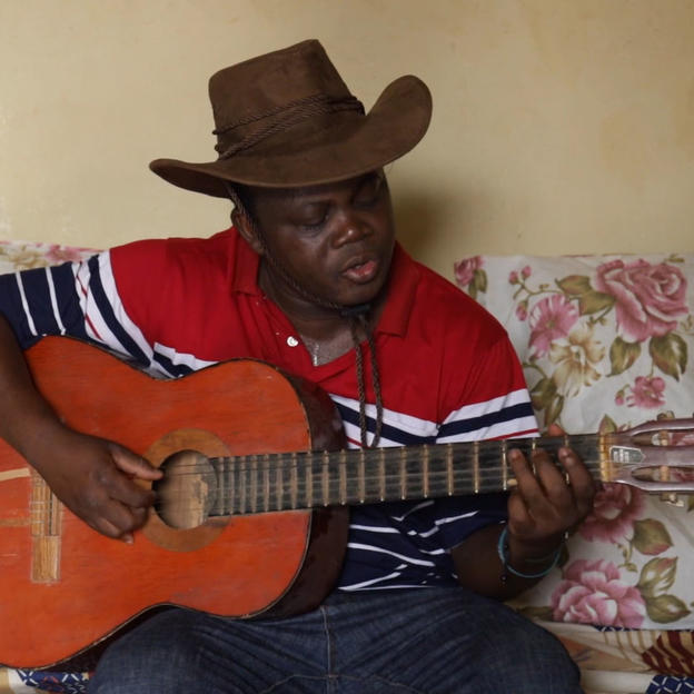 A screen grab from a video of Basile Ouedraogo playing guitar