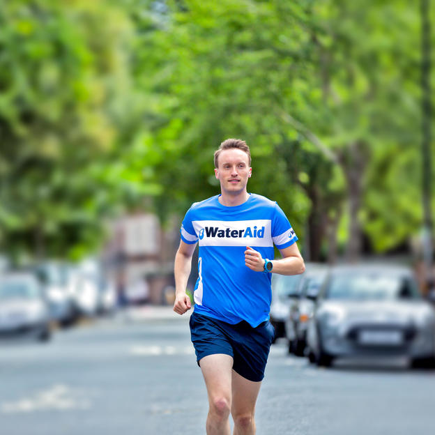 A WaterAid supporter running along the street, wearing a WaterAid t-shirt