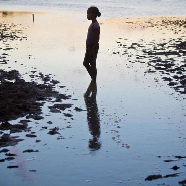 A young girl walks through a tidal pool near Morondava, Madagascar. When the rains came this whole area flooded and many families were affected. In Madagascar, 65% of the rural population live without access to clean water, while this southern African ...
