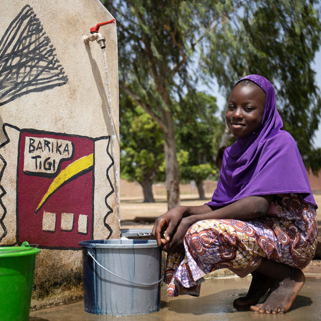 Aminata, a member of the school hygiene club, collecting water at a new tap in Mali.