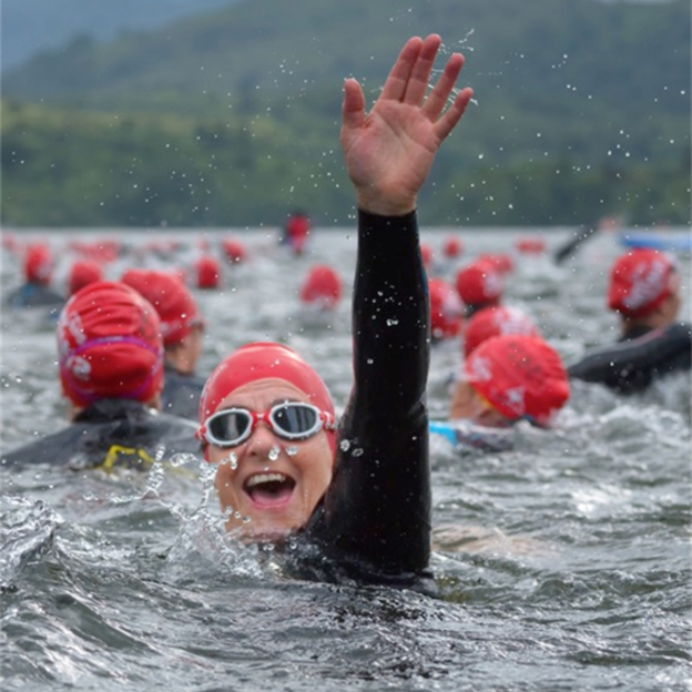 An outdoor swimmer smiles and raises their hand as they take part in a mass swim