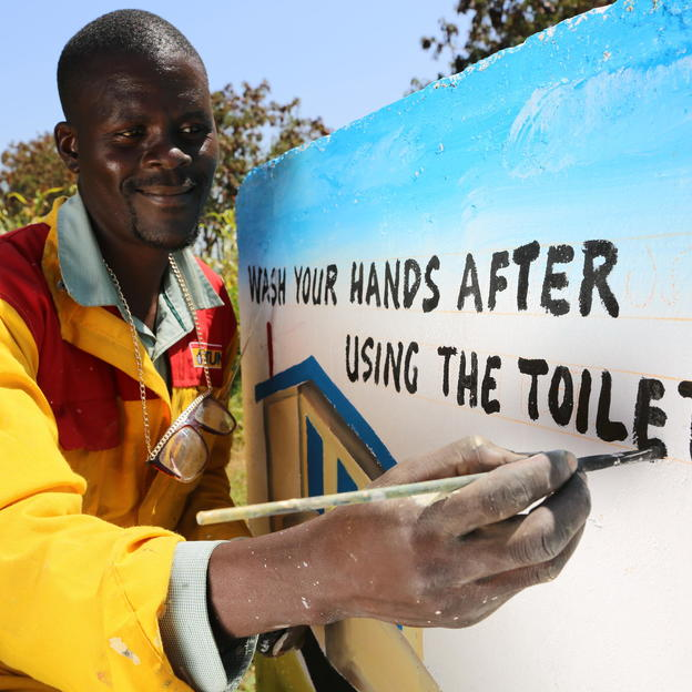Collins, an artists from Kenya, paints the wall of a primary school with a message about washing your hands after using the toilet