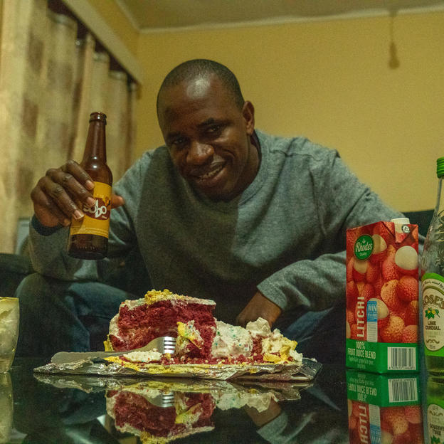 Dennis, inside his house, enjoying the red velvet birthday cake his wife made him. Covid-19 response. Lockdown Diaries - Dennis Lupenga. Malawi. May 2020