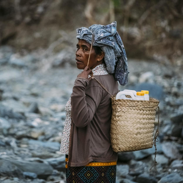 Felisberta da Costa, 57, carrying water in a basket on her back with headband walking along a rocky dried up river bed which is challenging underfoot to a water source to which the community have connected some homemade bamboo pipes to make a spout th ...