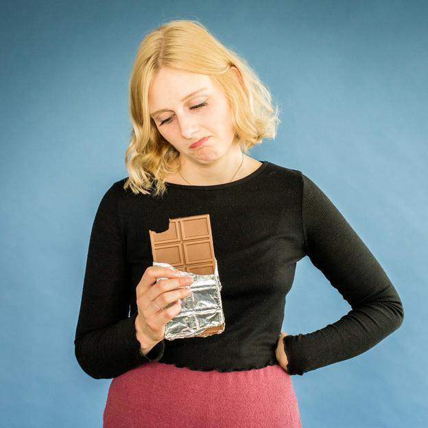 A woman holding a chocolate bar, which she's giving up for charity