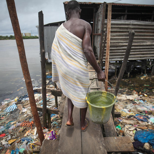Boakai, a fisherman from Libera entering the over water private latrine and bath