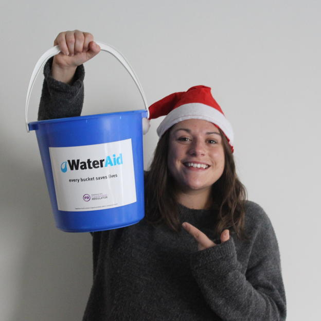 A fundraiser wearing a Christmas hat and holding a WaterAid bucket