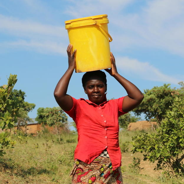 Majory Michelo, 37, carrying a bucket of water past the hills in Chitupa Village, in Monze District, Zambia, January 2018.