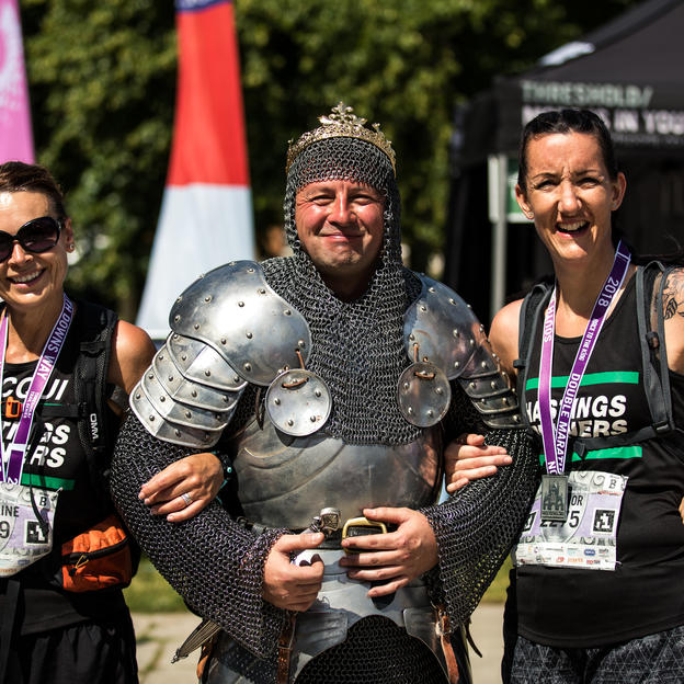 Racers pose with the King at the finish line of the Race to the King ultra marathon