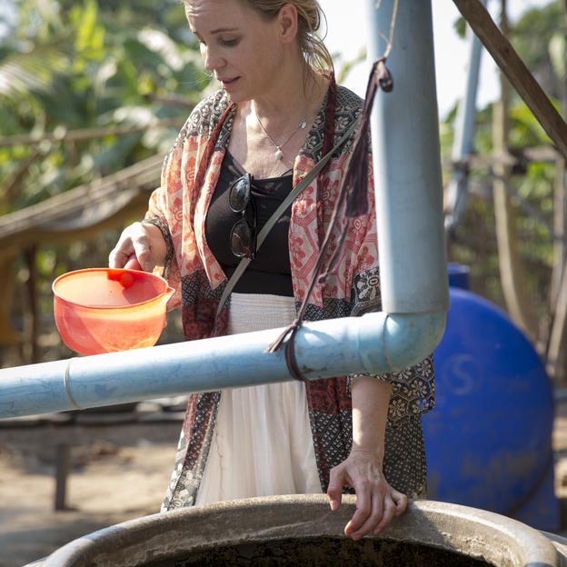 Sofia Helin, WaterAid Ambassador inspects the water storage at the home of Ven Tola in the village of Kampong Pnov.