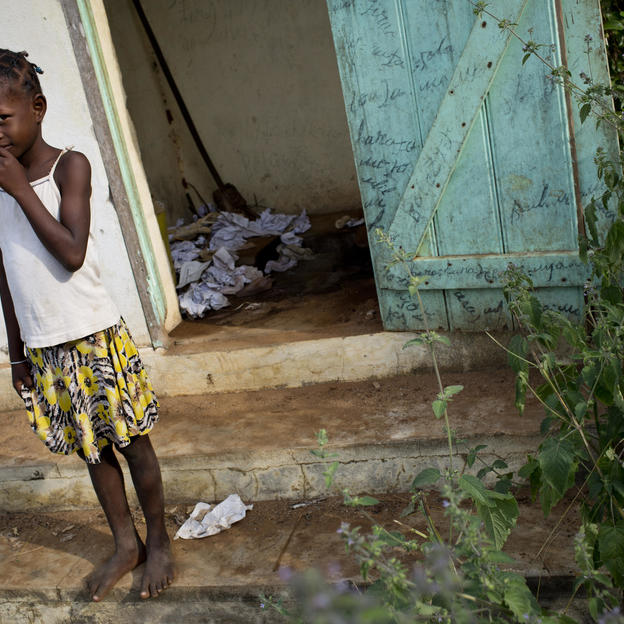 Zara stands next to latrines that are no longer fit for use at her school in Madagascar