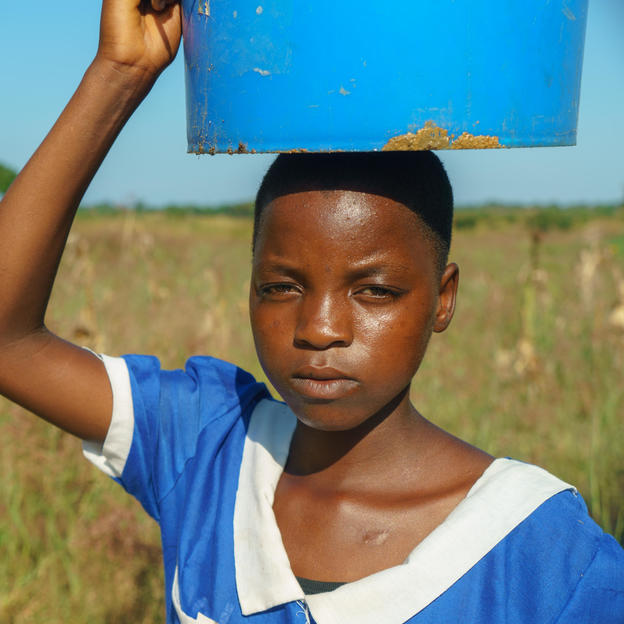 A girl carries a water bucket on her head as she walks outside