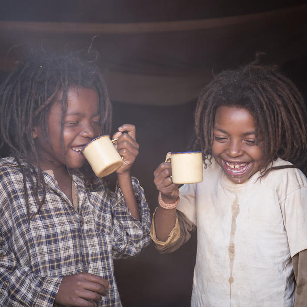 """We no longer fetch water far away from home anymore."" Faly, 9, with his young sister Kanto, 6, drinking a cup of tea at their home in Madagascar."