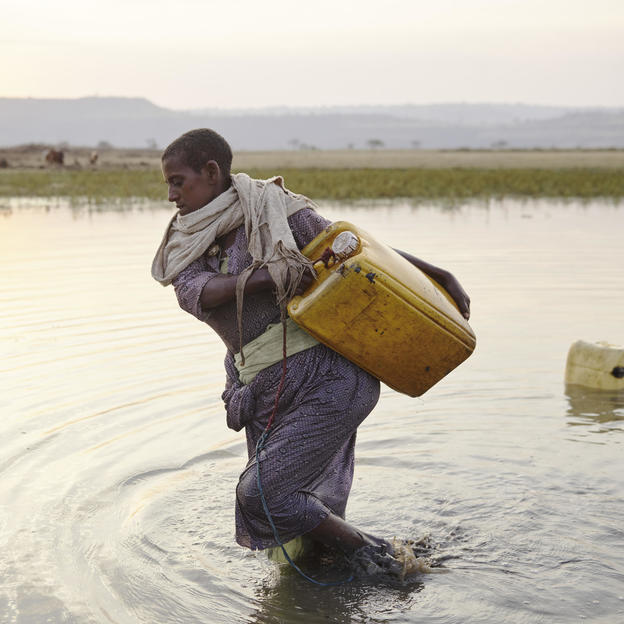 Yelfie Getaneh (35) collecting water from a large pond in Abechew, Frat, Ethiopia. February 2020