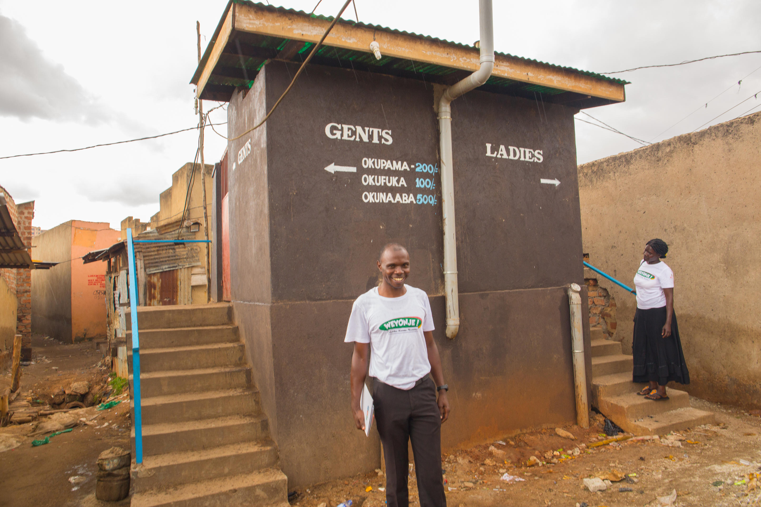 Chris inspecting a toilet that has been recently constructed by a landlord during a house to house WASH monitoring exercise in Kamwokya