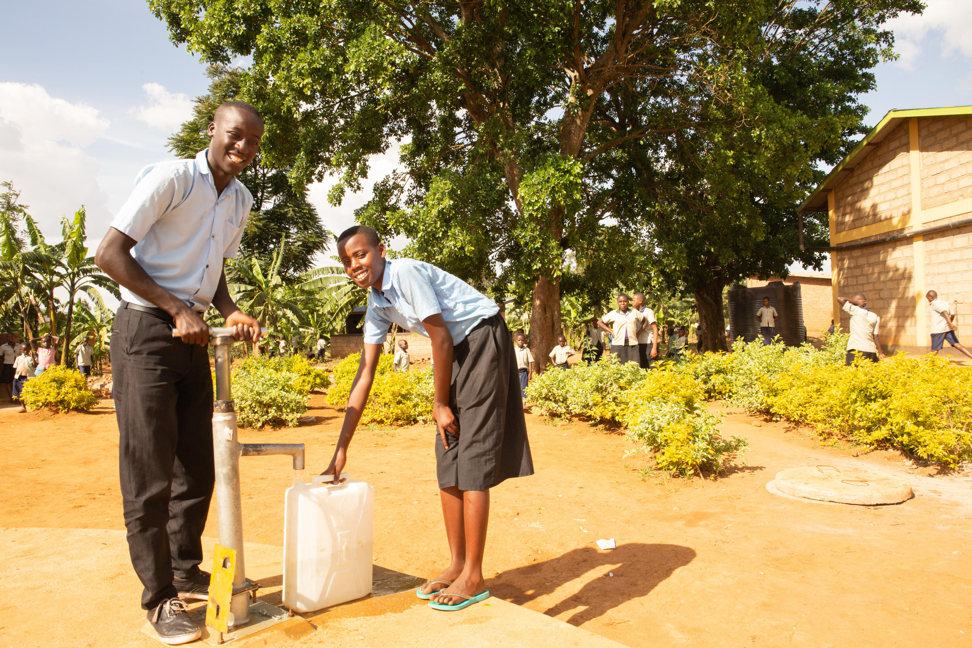 Twizeyimana Jean Bosco, 17, and his sister Claire Murekatete, 15, collecting water from new rain water harvesting tank, Rwanda, October, 2018.