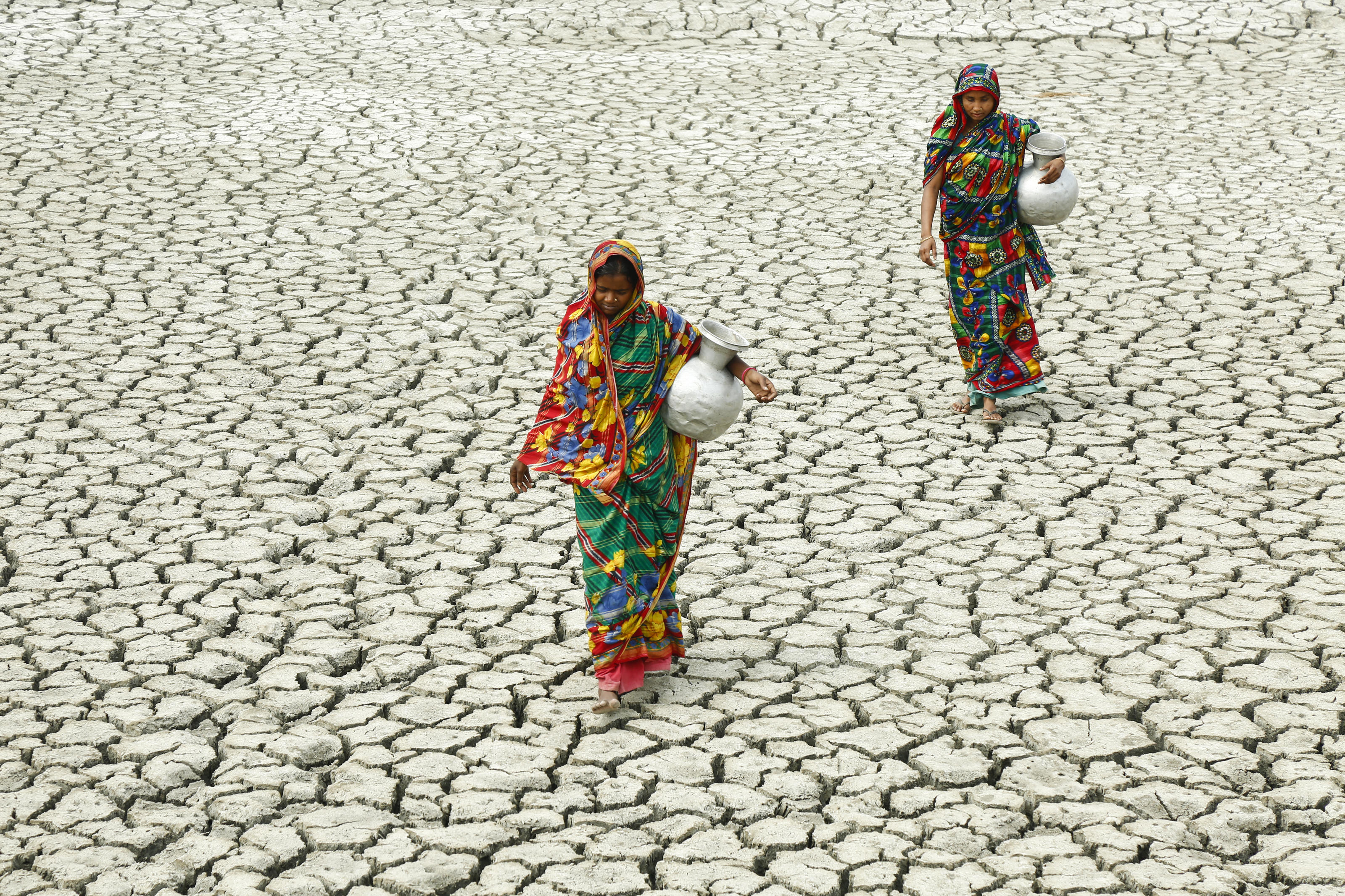 Village women walk on cracked ground, towards a pond to collect water. Floods, cyclones and droughts exacerbated by climate change make it extremely difficult to reach everyone with clean water, toilet and hygiene services. In the south of Bangladesh, ...