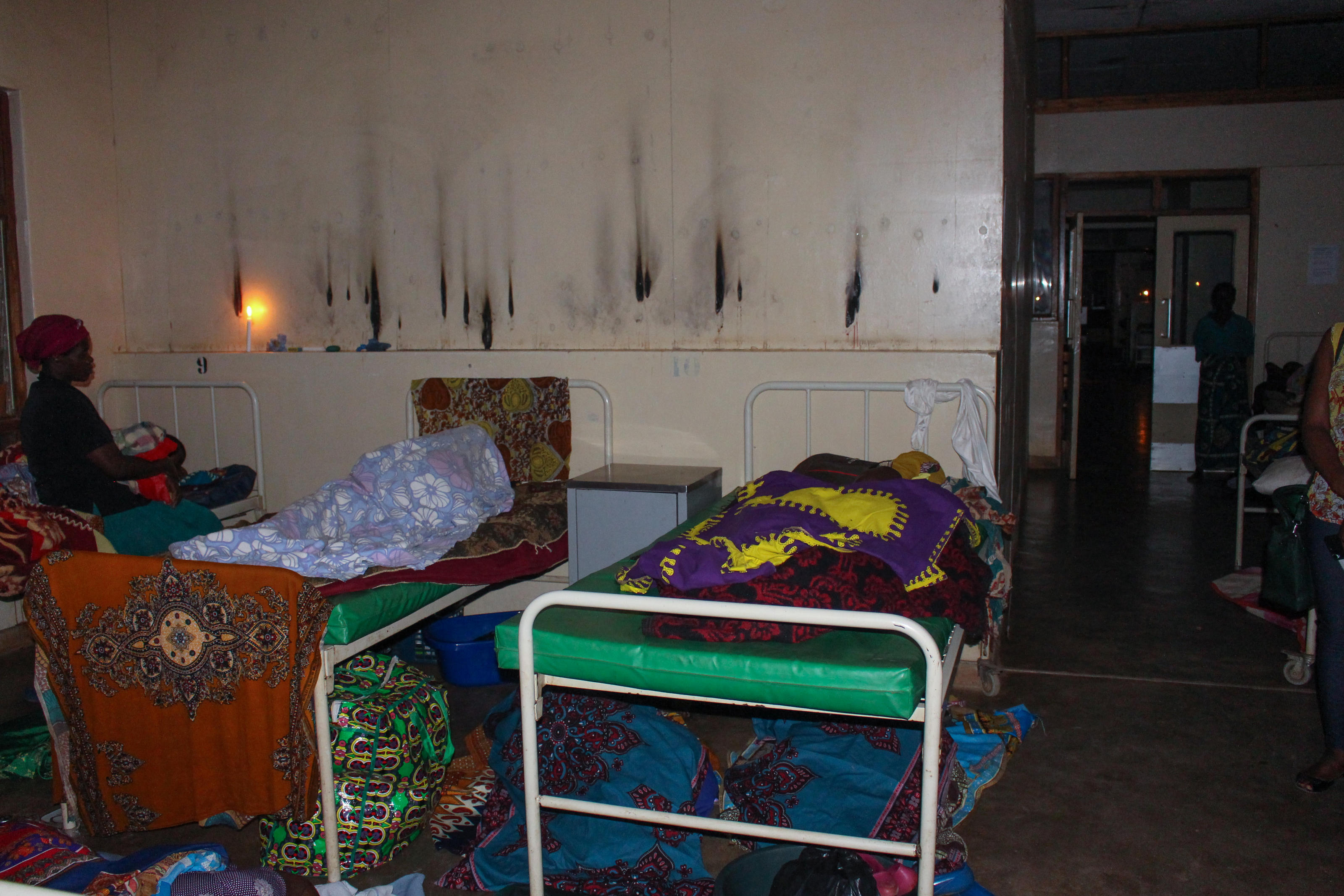 In the maternity ward, expectant women and their guardians sleep in the dark, aided by candlelight, in Ntchisi District Hospital, Malawi, October 2018.