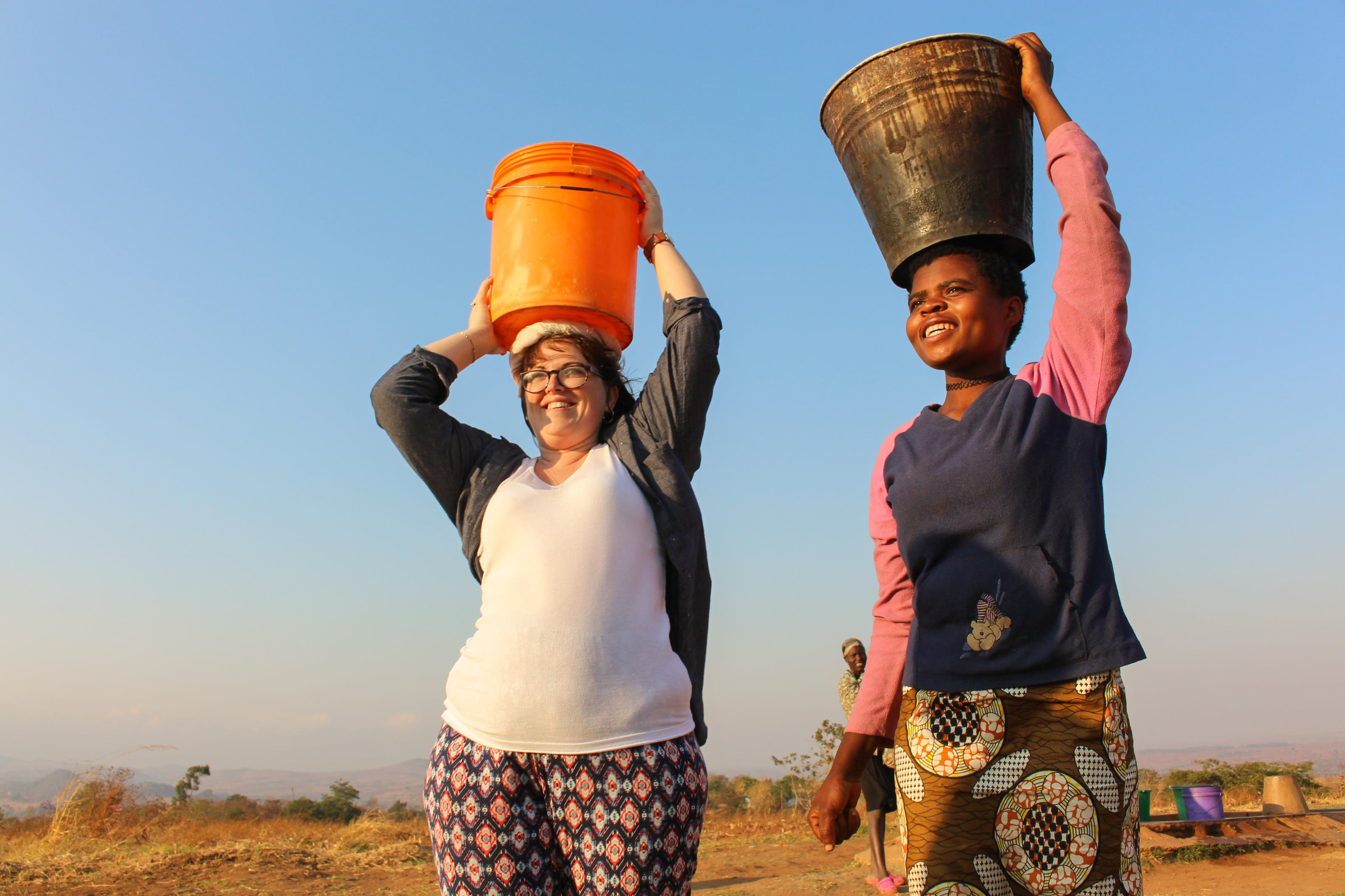 Elizabeth McKernan from WaterAid Scotland helps carry water back to Ntchisi District Hospital from the nearest borehole