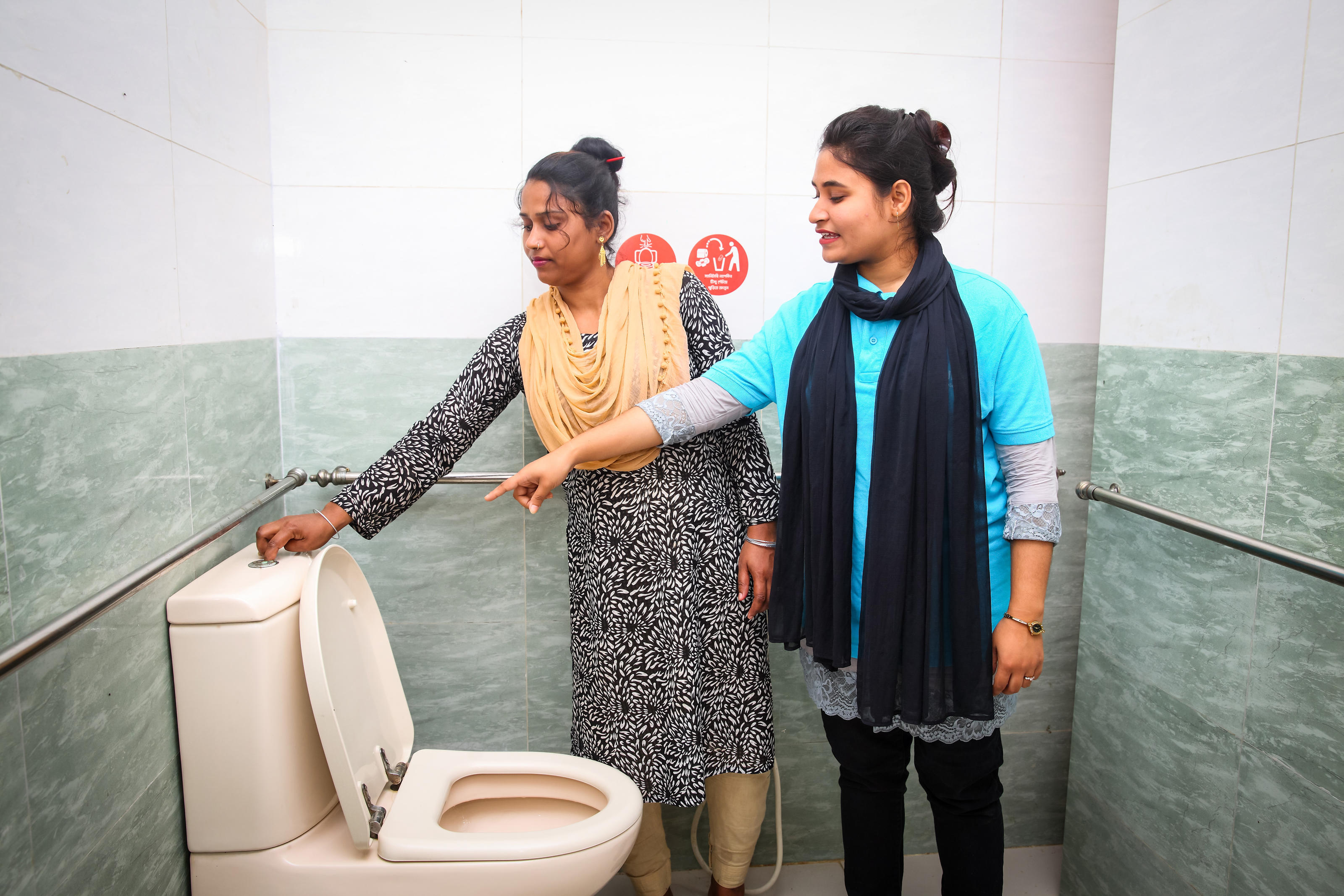 Nazma learning about the new toilet facilities with volunteer Habiba