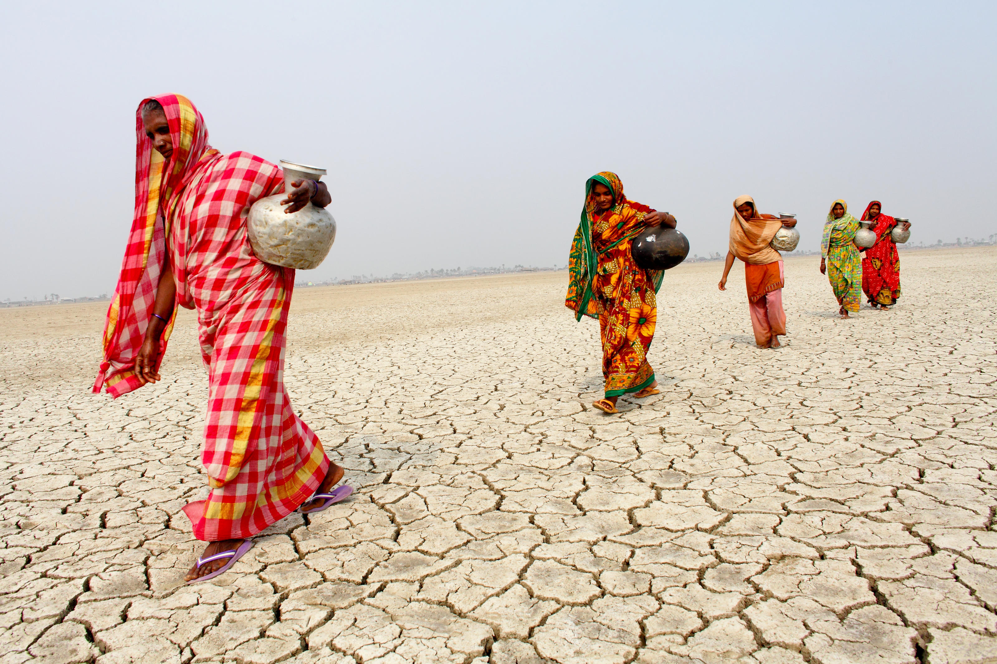 When collecting water from the local community in Koyra, Bangladesh, women must walk across an area of barren ground that has been contaminated with saline following cyclone Aila in 2009.