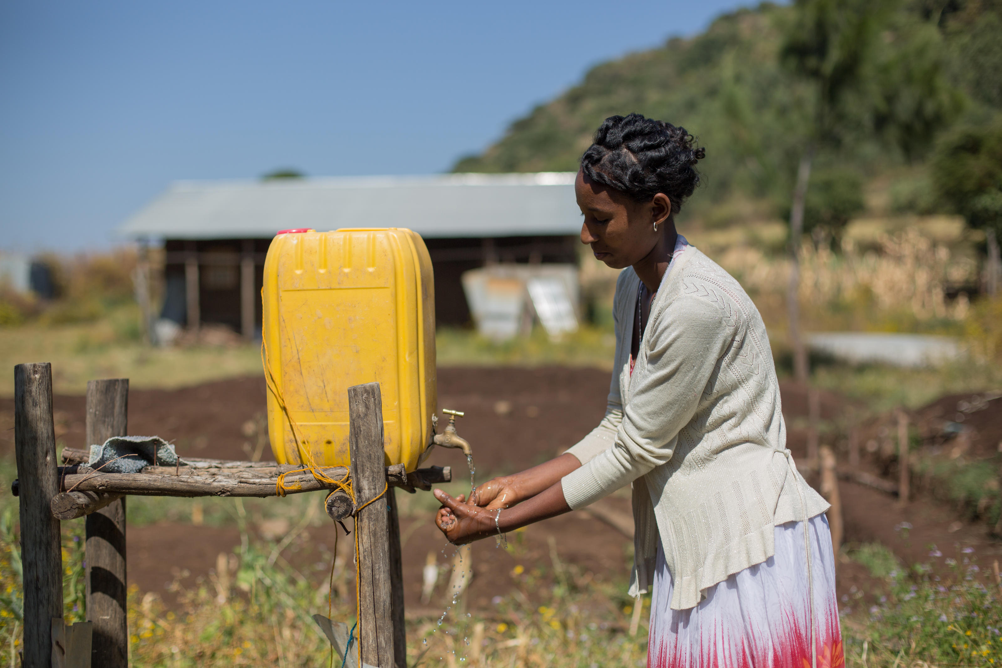 Yehasab Ayenew, 24, a cleaner, washing her hands using the 20 litres of water set aside for hand washing at Yiraber Health Centre, Ethiopia
