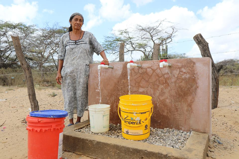 Woman collecting water from tap near her house in Colombia.