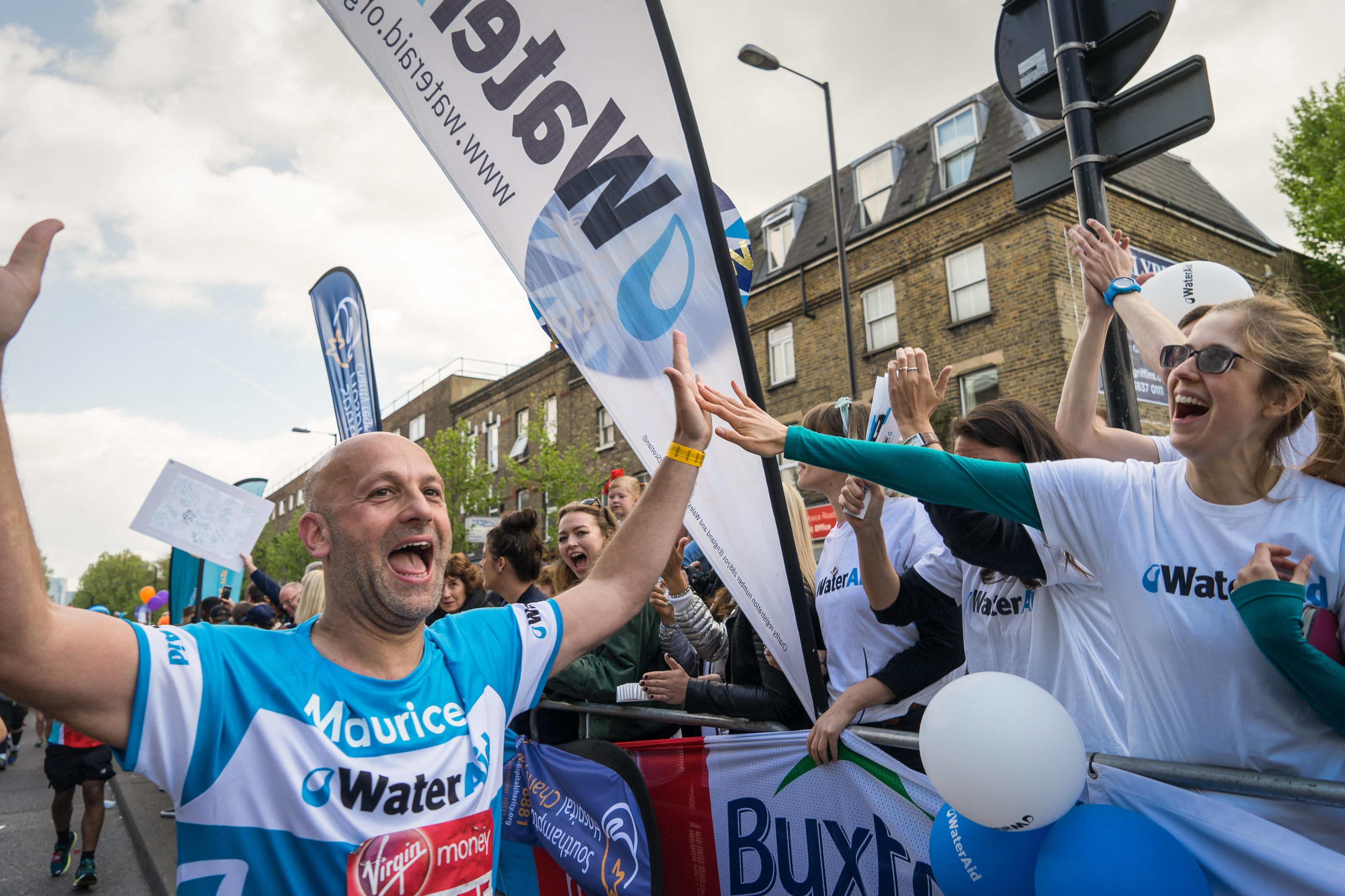 WaterAid runner being cheered on by supporters in the Virgin London Marathon, April 2017