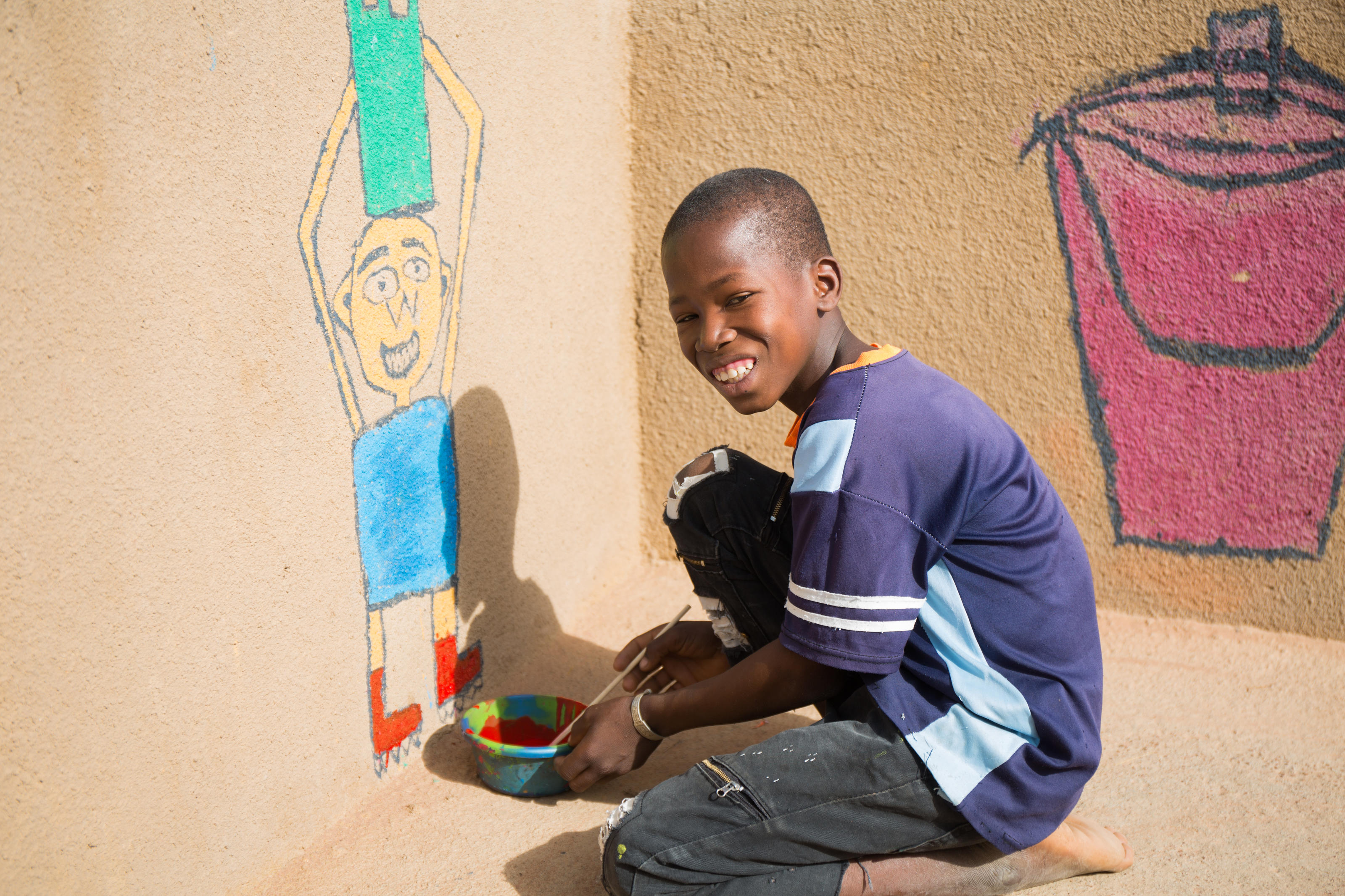 Dramane, 13, a sixth year pupil at Wakoro undergraduate school, doing some murals at the borehole in the district of Bla, Segou, Mali, October 2018.